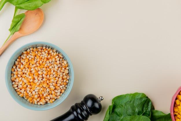 Vista superiore della ciotola di semi di mais con spinaci e cucchiaio di legno su bianco con lo spazio della copia