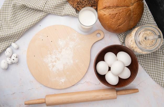 Vista superiore della ciotola di uova e tagliere con mattarello e pane di pannocchia di avena-fiocchi di latte sulla superficie bianca