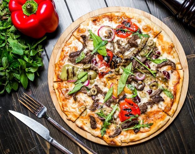 Vista superiore della cipolla del formaggio del pomodoro della rucola del basilico del peperone dolce della pizza della carne