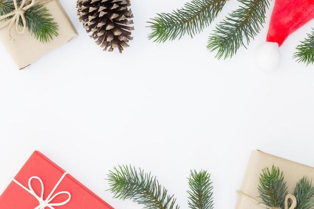 Vista superiore della composizione di natale, confezione regalo, pigne, rami di abete su sfondo bianco e copia spazio per informazioni di testo
