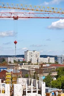 Vista superiore della costruzione di un nuovo edificio e due gru a torre su uno sfondo di città moderna, messa a fuoco selettiva