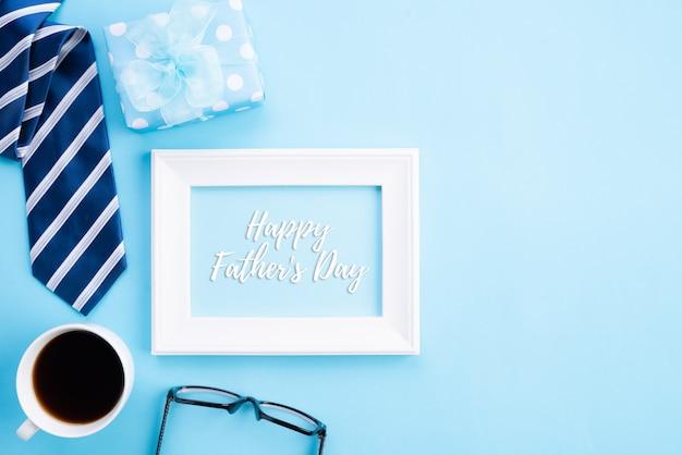 Vista superiore della cravatta blu, bella confezione regalo, tazza da caffè, cornice bianca