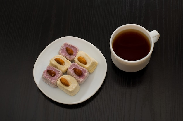 Vista superiore della delizia turca con mandorle e tazza di caffè, tavolo nero
