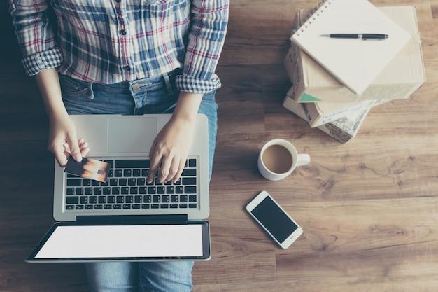 Vista superiore della donna che compera online con carta di credito tramite computer portatile da casa