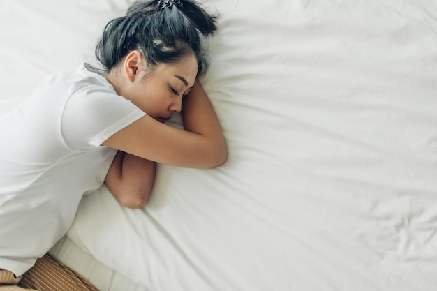Vista superiore della donna che dorme sul suo letto con lo spazio bianco della copia.