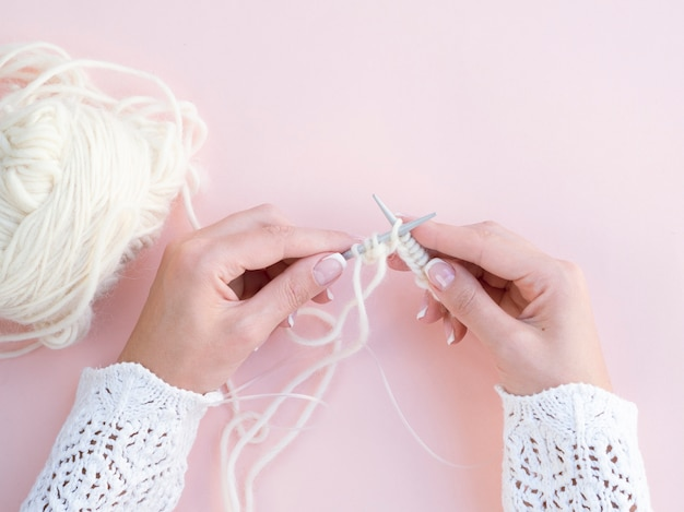 Vista superiore della donna che lavora all'uncinetto lana bianca