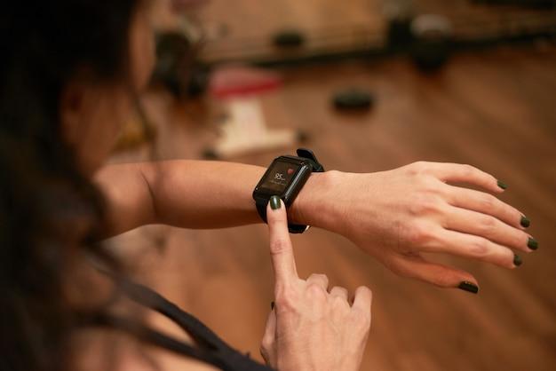 Vista superiore della donna irriconoscibile che controlla l'app di salute sul suo gadget da polso