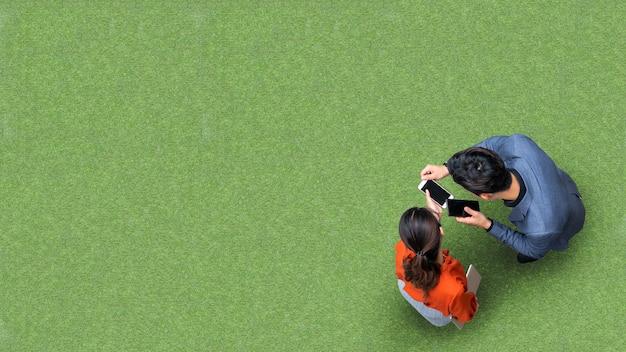 Vista superiore della gente della donna e dell'uomo d'affari che si incontra e che per mezzo dello smartphone