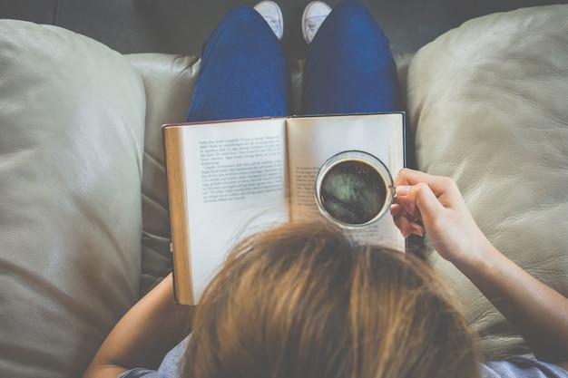 Vista superiore della giovane donna che legge un libro e che tiene tazza di caffè
