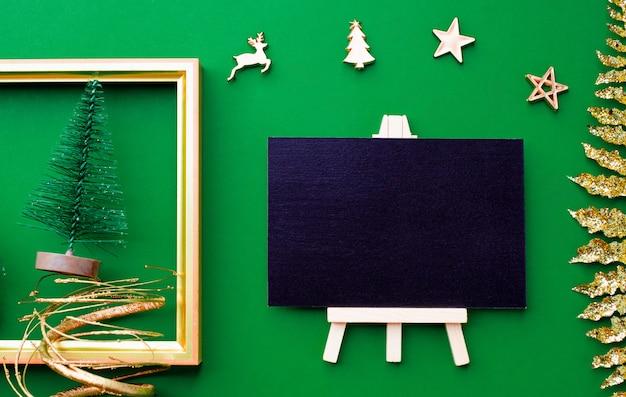 Vista superiore della lavagna con roba dell'ornamento della decorazione di natale e del nuovo anno dell'oro su fondo verde