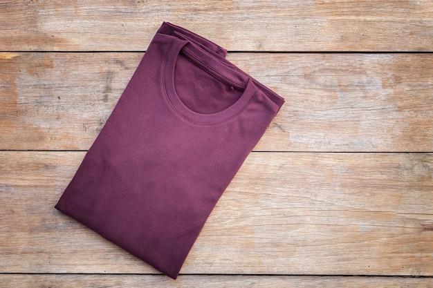 Vista superiore della maglietta di colore su priorità bassa di legno grigia della plancia