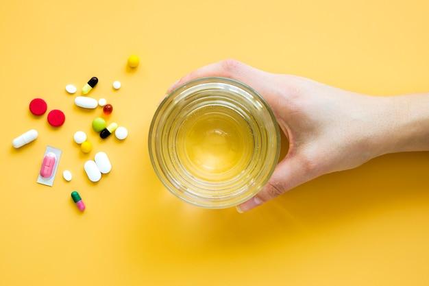 Vista superiore della mano che tiene bicchiere d'acqua con le pillole
