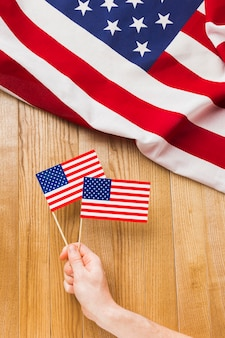 Vista superiore della mano che tiene le bandiere americane