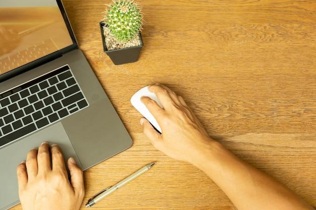 Vista superiore della mano dell'uomo di affari facendo uso del computer portatile e tenendo topo con la penna sullo scrittorio di legno.