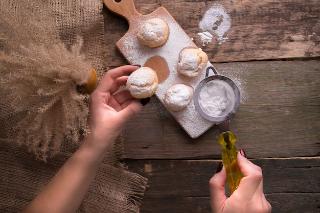 Vista superiore della mano della donna che decora con lo zucchero a velo alcuni profiteroles. stile rustico.