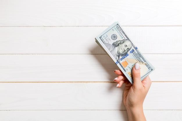 Vista superiore della mano femminile che dà cento banconote in dollari su fondo di legno. concetto di carità e donazione con spazio di copia
