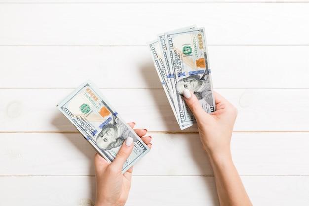 Vista superiore della mano femminile che dà dei soldi, primo piano di conteggio delle cento banconote in dollari