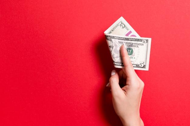Vista superiore della mano femminile che tiene un pacco di soldi. cinque dollari. concetto di affari con spazio vuoto per il vostro disegno. concetto di beneficenza e suggerimenti