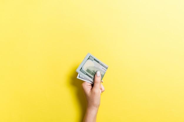 Vista superiore della mano femminile in possesso di un pacco di soldi su sfondo colorato. cento dollari. concetto di affari con spazio vuoto per il vostro disegno. concetto di beneficenza e suggerimenti
