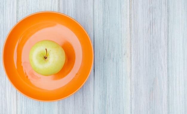 Vista superiore della mela verde in piatto su fondo di legno con lo spazio della copia