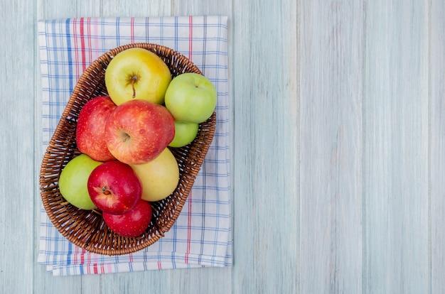 Vista superiore della merce nel carrello delle mele sul panno del plaid e sul fondo di legno con lo spazio della copia
