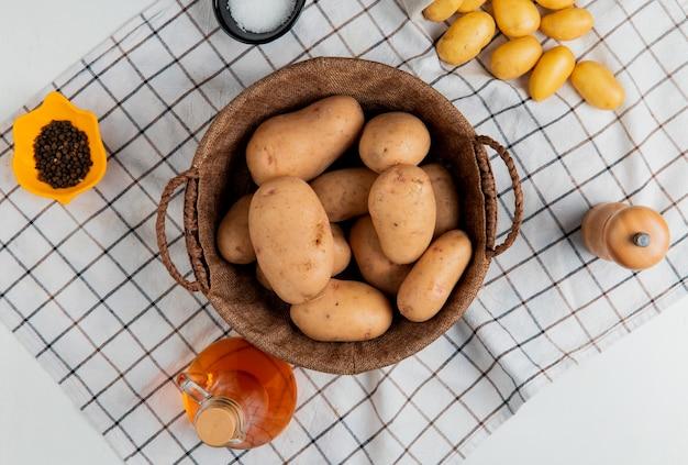 Vista superiore della merce nel carrello delle patate con pepe nero del sale del burro sul panno del plaid e sulla superficie bianca