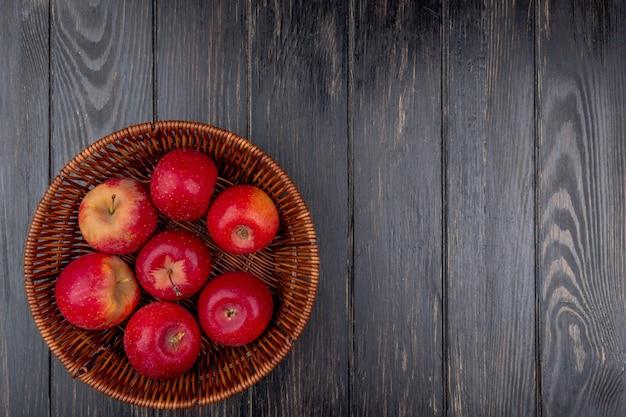 Vista superiore della merce nel carrello rossa delle mele su fondo di legno con lo spazio della copia