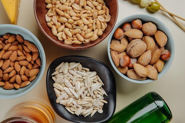 Vista superiore della miscela degli spuntini della birra dei semi di girasole matti e delle arachidi salate con una bottiglia di birra su bianco