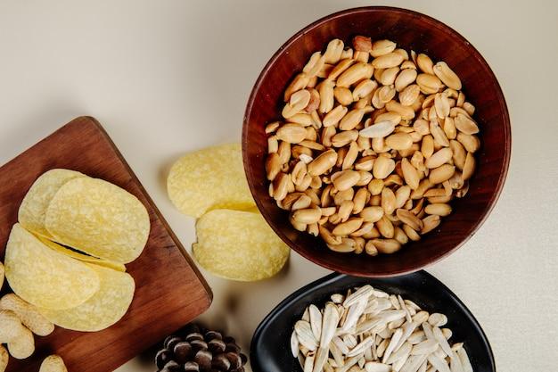 Vista superiore della miscela degli spuntini salati alla birra delle arachidi in una ciotola di legno patatine fritte e semi di girasole su bianco