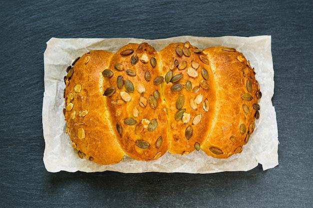 Vista superiore della pagnotta di pane con semi di zucca sul bordo di pietra ardesia nera