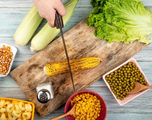 Vista superiore della pannocchia di mais del taglio manuale della donna con il coltello sul tagliere e semi del cereale del sale della lattuga dei piselli su superficie di legno