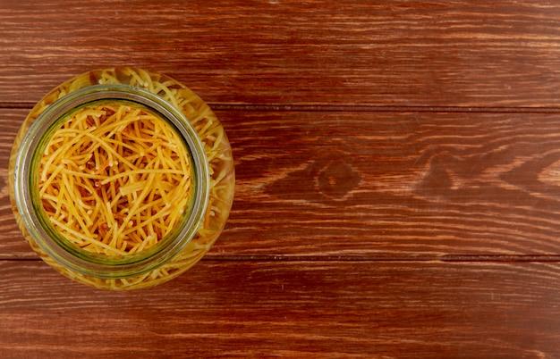 Vista superiore della pasta degli spaghetti in ciotola su superficie di legno con lo spazio della copia