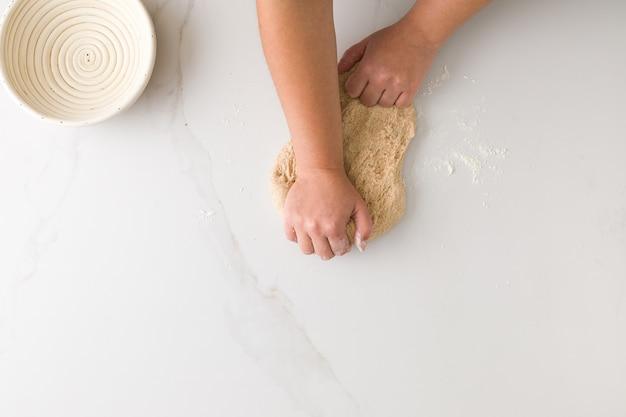Vista superiore della pasta di pane d'impastamento della mano femminile in una tavola di marmo con una ciotola di pane vuota con spazio per testo