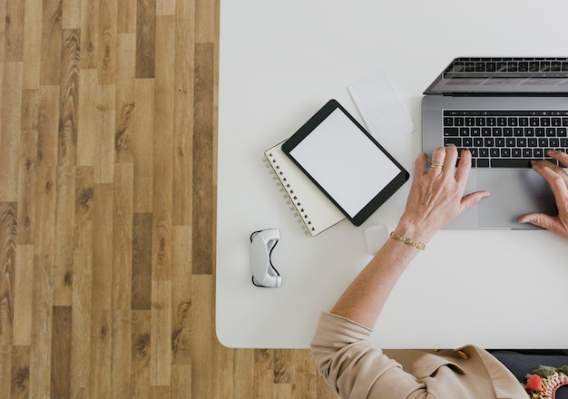 Vista superiore della persona che scrive sul computer portatile e sulla compressa del modello con copyspace