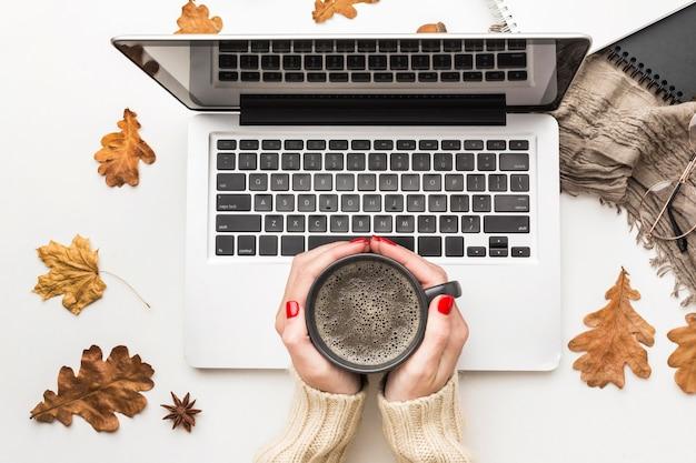 Vista superiore della persona che tiene la tazza di caffè con il computer portatile