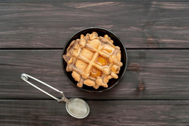 Vista superiore della pila di cialde sul piatto con miele e setaccio