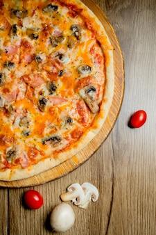 Vista superiore della pizza salsiccia con pomodoro funghi e formaggio