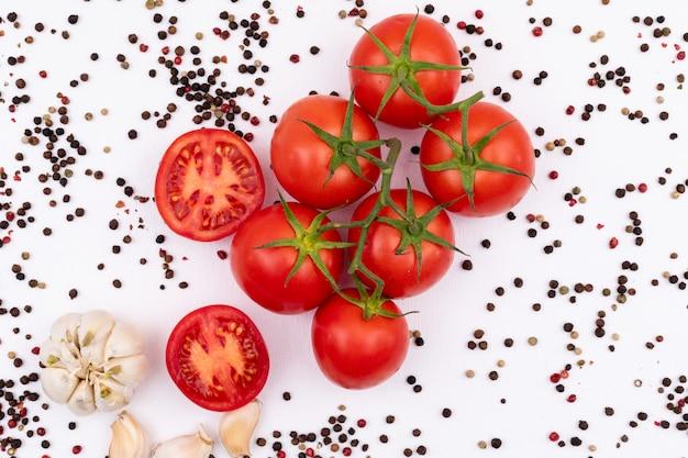 Vista superiore della polvere del pepe nero dell'aglio e dei pomodori su superficie bianca