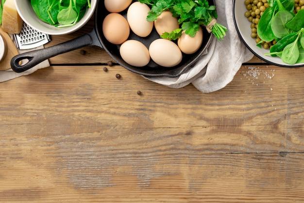 Vista superiore della prima colazione sana con l'ingrediente per cucinare. piselli, uova, spinaci, prezzemolo e formaggio su fondo di legno con la vista superiore del copyspace