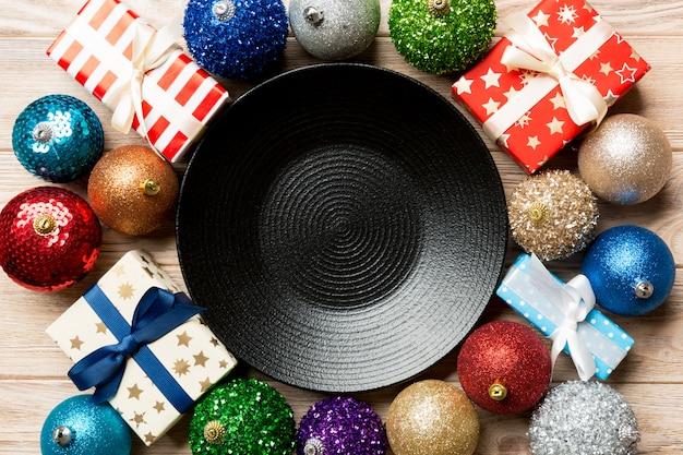 Vista superiore della regolazione di festa su legno, piatto, regali, bagattelle e decorazioni natalizie, concetto di cena di capodanno