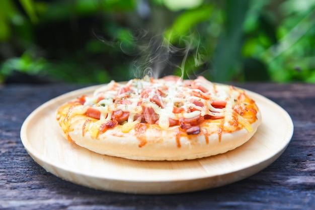 Vista superiore della salsa di formaggio della pizza su fondo di legno rustico