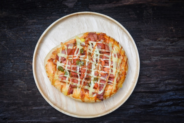 Vista superiore della salsa di formaggio della pizza sul ketchup di hot dog delle salsiccie della guarnizione della pizza della superficie di legno rustica