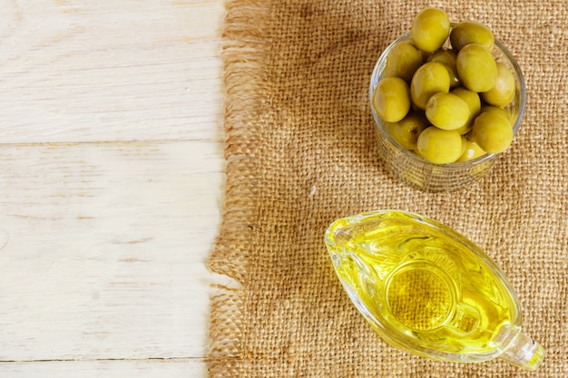 Vista superiore della salsiera di vetro con olio extra vergine di oliva e olive verdi fresche sul panno di tela sulla tavola di legno.