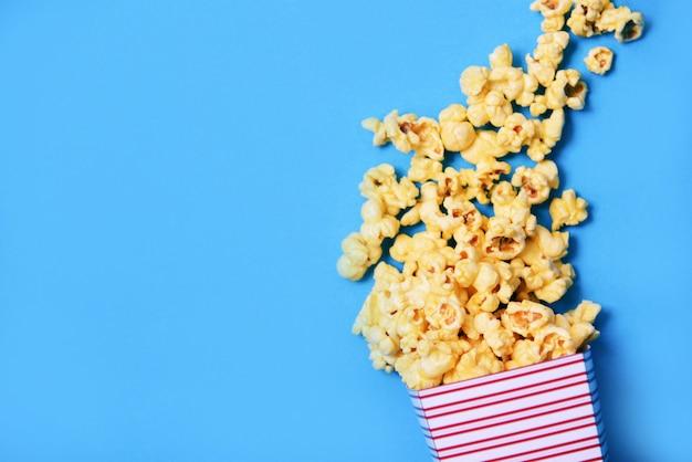 Vista superiore della scatola della tazza di popcorn e del backgroubd blu / sale del popcorn del burro dolce