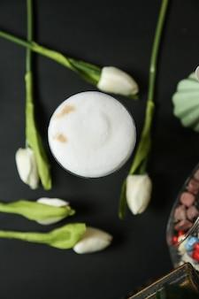 Vista superiore della schiuma del latte alla cannella del caffè espresso del latte del caffè nero del latte