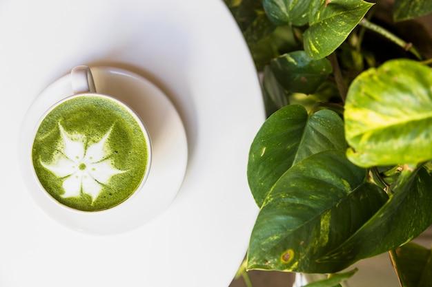 Vista superiore della schiuma di tè verde matcha caldo sul tavolo bianco con foglie verdi