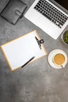 Vista superiore della scrivania con computer portatile, caffè, pianta in vaso, taccuino e appunti