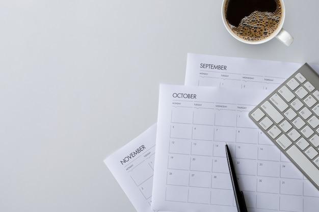 Vista superiore della scrivania con la tazza di caffè, la tastiera e l'orario di lavoro sulla tavola bianca