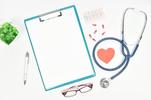 Vista superiore della scrivania del medico con stetoscopio, occhiali, droga e carta bianca negli appunti.