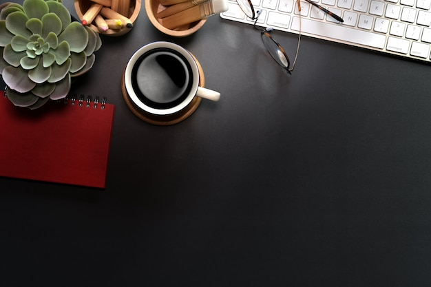 Vista superiore della scrivania nera con computer tastiera, forniture per ufficio e lo spazio della copia